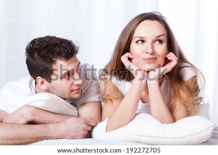 A stubborn confident woman and a loving shy man lying in bed