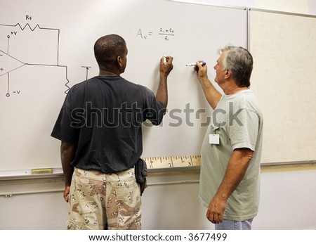 A student and teacher working equations on the board. - stock photo