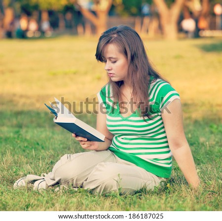 A student in the courtyard of the university with books in their hands. Vintage retro hipster style version - stock photo
