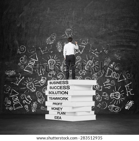 A student is drawing chalk business icons on the wall. Business books' pedestal. - stock photo