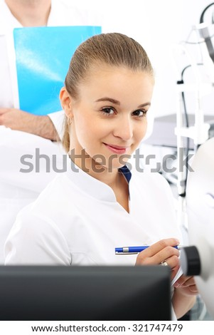 A student of medicine at practice.  Young attractive doctor ophthalmologist at an ophthalmologist