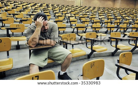 A student sits alone in a sea of empty seats in a lecture hall - stock photo