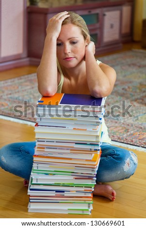 a student sits in front of a stack of books to learn the - stock photo
