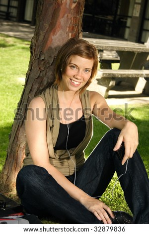 A student sitting next to  a tree listening to her music - stock photo