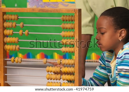 A student solving  a math assignment using an abacus - stock photo