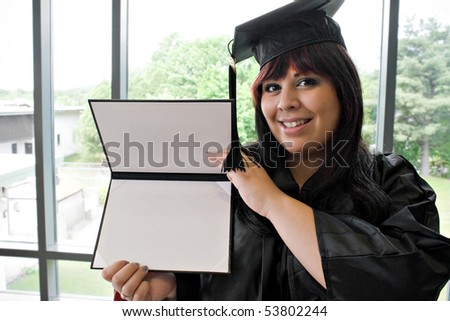 A student that recently had a school graduation posing proudly with her diploma indoors. - stock photo