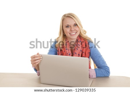 a student working on her laptop with a big smile on her face.