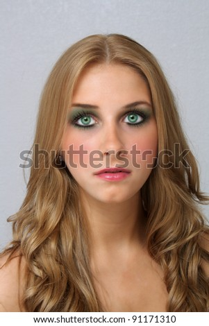 A studio close-up of a lovely young blonde with captivating eyes.