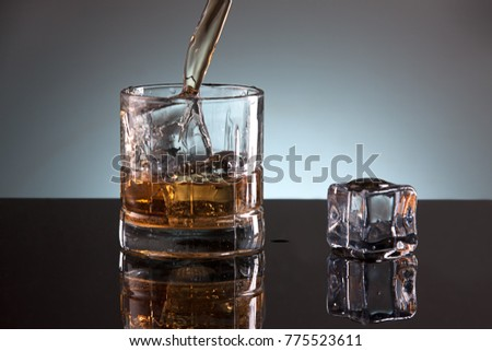 A studio image of a glass filled with ice and liquor.
