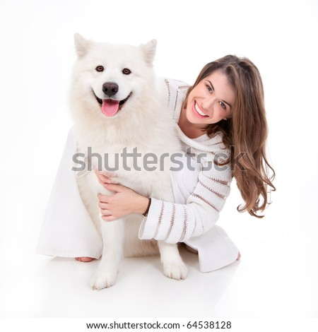 a studio image of a young woman, dressed in white, with her white dog, huging it, both posing, looking happy and smiling - stock photo
