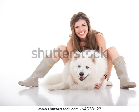 a studio image of a young woman hugging her white dog, which she holds in front of her, looking forward and smiling.