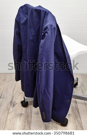 A studio photo of a light summer jacket hanging over a business chair