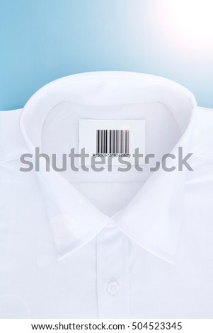 A studio photo of a white business shirt with a barcode
