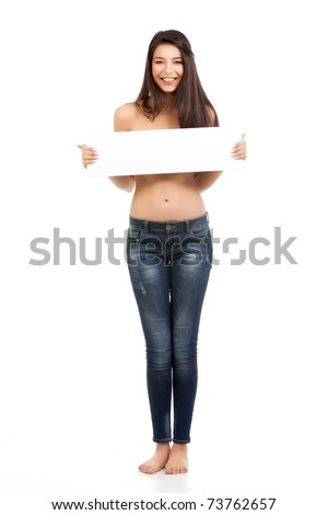 a studio portait of a beautiful, young woman, smiling, dressed only in her blue jeans, holding a white board in front of her breasts - stock photo