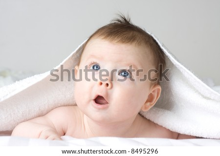 A studio portrait of a beautiful little caucasian white baby girl with blue eyes and cute facial expression looking up - stock photo