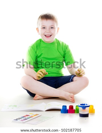 a studio portrait of a nice boy drawing with watercolor paint and brush isolated on white background