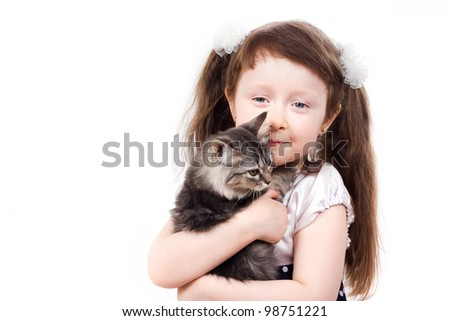 a studio portrait of a smiling little girl holding a kitten in her hands isolated on white background