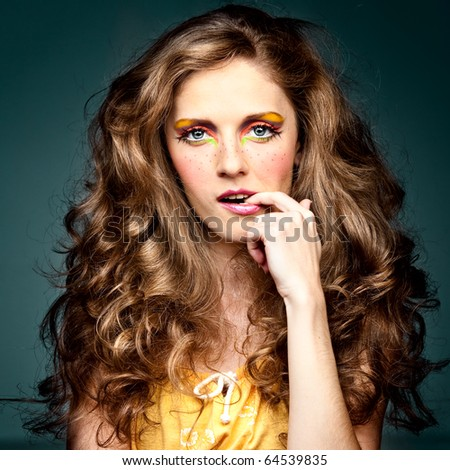 a studio portrait of a young woman with long, blonde and wavy hair and blue eyes. her make-up is very colorful; it is inspired by the '60s style and she has freckles drawn on her cheeks. - stock photo