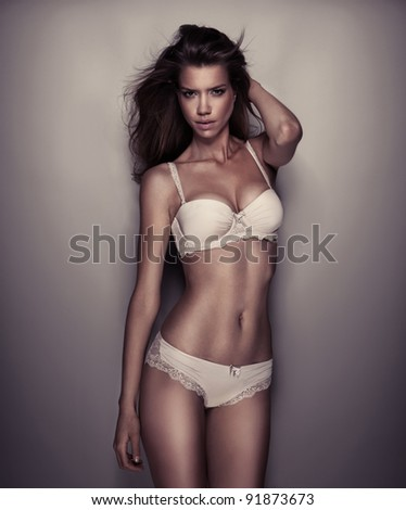 A studio shot of a beautiful and sexy girl with long hair wearing white lingerie - stock photo