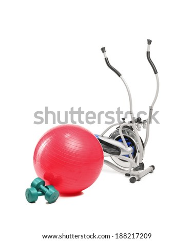 A studio shot of a cross trainer machine, pilates ball and dumbbells isolated on white background - stock photo