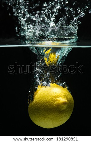 A studio shot of a lemon entering water with a crown of water above surface - stock photo
