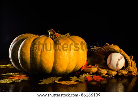 A studio shot of a pumpkin and a baseball glove and ball with fall leaves.