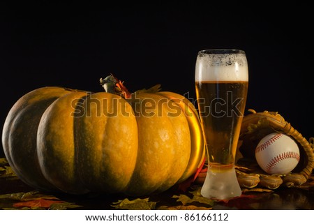 A studio shot of a pumpkin and a baseball glove, ball and a tall beer. - stock photo