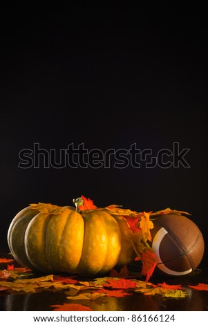 A studio shot of a pumpkin and a football with fall leaves. - stock photo