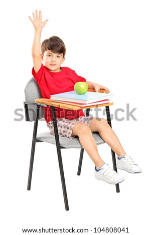 A studio shot of a schoolboy seated in a chair raising his hand isolated on white background - stock photo