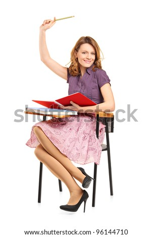 A studio shot of a schoolgirl raising her hand isolated on white background - stock photo