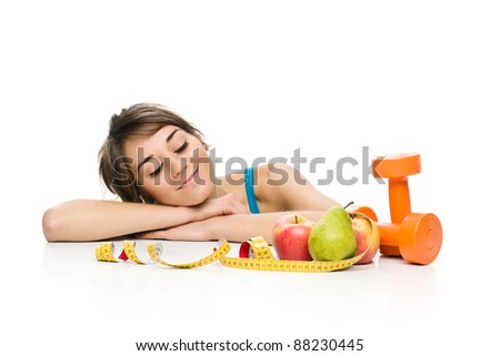 A studio shot of an attractive healthy young woman (personal trainer or exercise enthusiast) with fruits and a dumbbell. - stock photo
