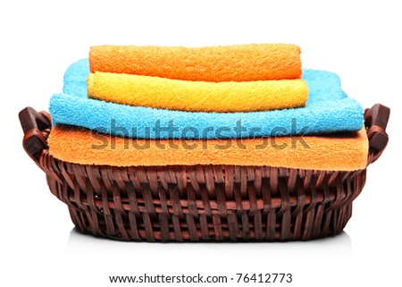 A studio shot of colorful towels in a basket isolated on white background - stock photo