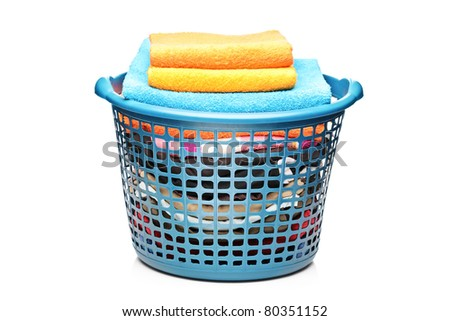 A studio shot of colorful towels in a laundry bin isolated on white background - stock photo
