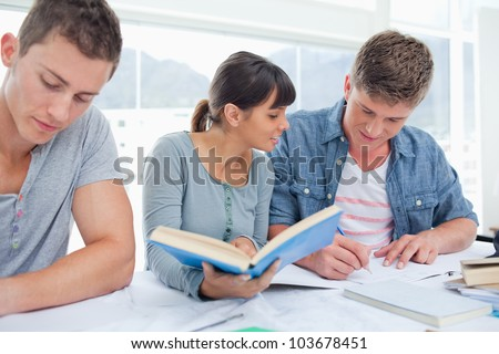 A studying group of students sit together and use books to help them