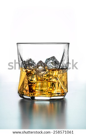 a stunning whiskey glass with ice - whiskey in the rocks - stock photo