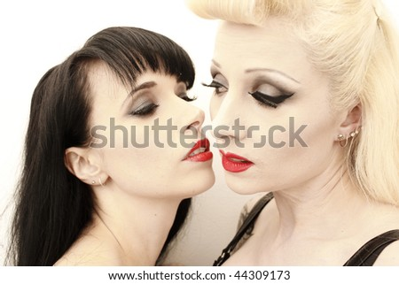 a stunning woman being seduced by another woman. - stock photo