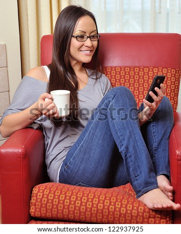 A stunning young biracial woman (Caucasian and Asian) smiles as she holds a mug of coffee while reading a text message on her cell phone - stock photo