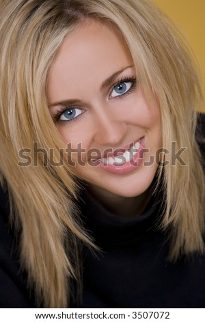 A stunningly beautiful young woman with blond hair and fantastic blue eyes smiling a gorgeous smile.