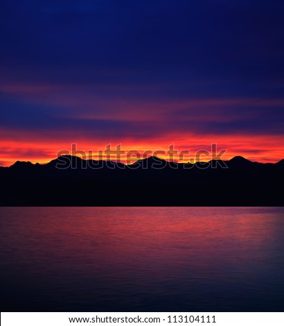 A Stunningly Brilliant Sunrise Over Mountains And The Waters Of Lake Mead At The Border Between Nevada And Arizona, This Is A Fictionalized Photo Composite - stock photo