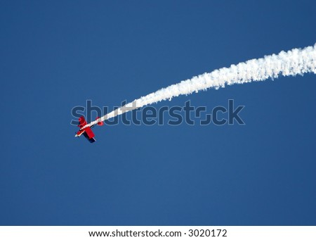 A stunt airplane performs a inverted roll at an airshow. Bright blue sky