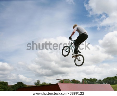 A stunt rider doing high jumps on a bmx bicycle - stock photo
