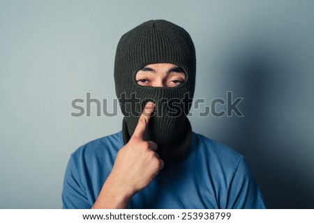 A stupid man wearing a balaclava is trying to pick his nose - stock photo
