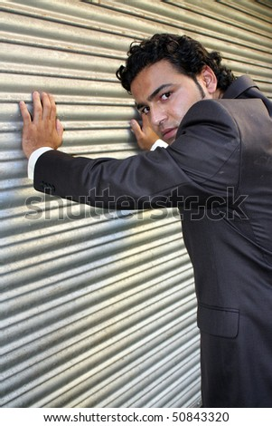 A stylish angry businessman posing near a shutter. - stock photo