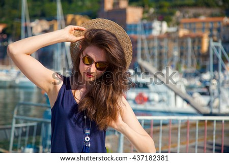 A stylish brunette model girl wearing casual blue pants and top and sunglasses enjoying her Italian summer vacation on Amalfi Coast, Italy. - stock photo