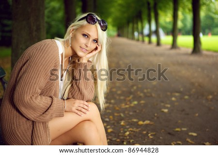 A stylish glamorous blonde woman sits in an empty tree-lined park avenue enjoying the peace and solitude. - stock photo