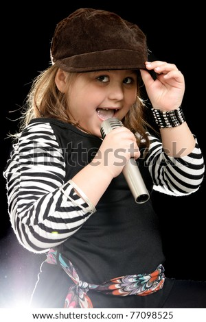 A stylish little girl is sing into a microphone, shot with a backlight - stock photo