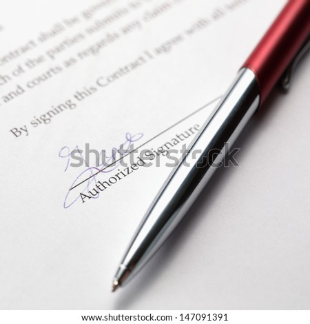 A stylish pen laying over a signed contract. - stock photo
