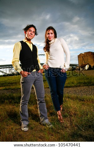 A stylish young couple stands in front of a dramatic sky in an empty lot in an urban setting. - stock photo