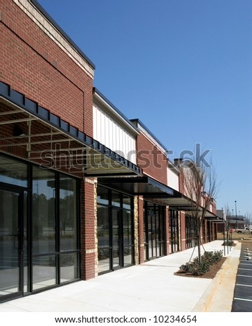 A suburban shopping center made of textured brick, stone, and glass in the final stage of construction.
