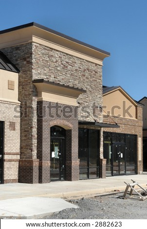 A suburban shopping center under construction.  A stone and brick storefront. - stock photo